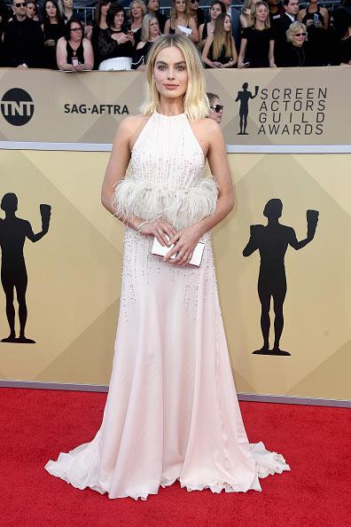 Margot Robbie dans une robe longue agrémenté de plumes sur la taille