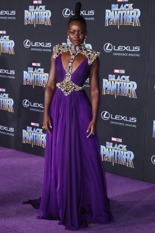 Lupita N'yongo en une robe de cocktail prune longue découpé & orné de strass