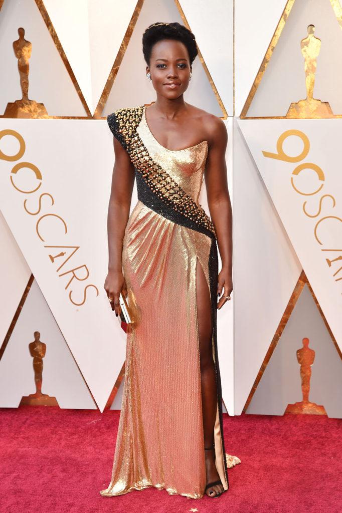 Lupita Nyong'o en une robe de soirée dorée longue asymétrique avec fente