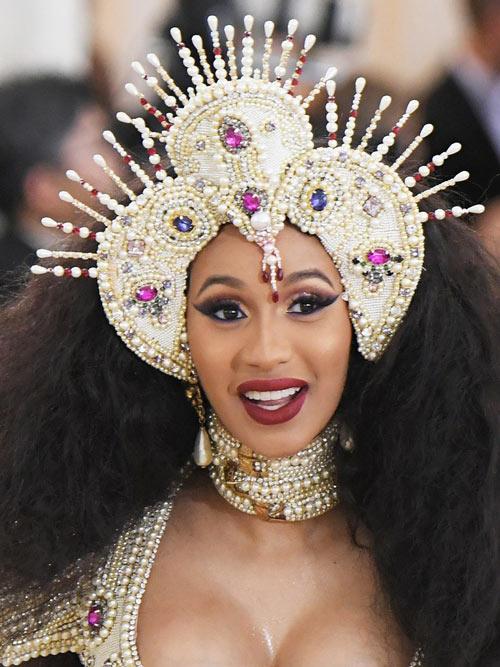 Cardi B portait un chapeau de tri-point couvert de perles, de strass et de bijoux et le maquillage rose-oeil fumé